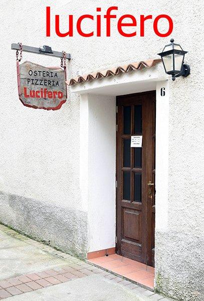 una porta d'entrata in legno vista dall'esterno e un'insegna Osteria Pizzeria Lucifero