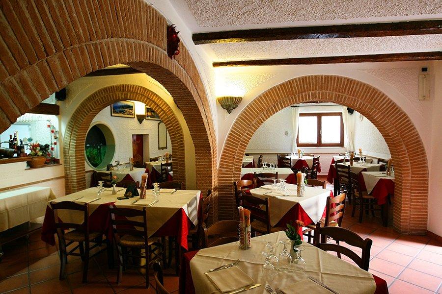 Interni del ristorante con tavoli apparecchiati e archi