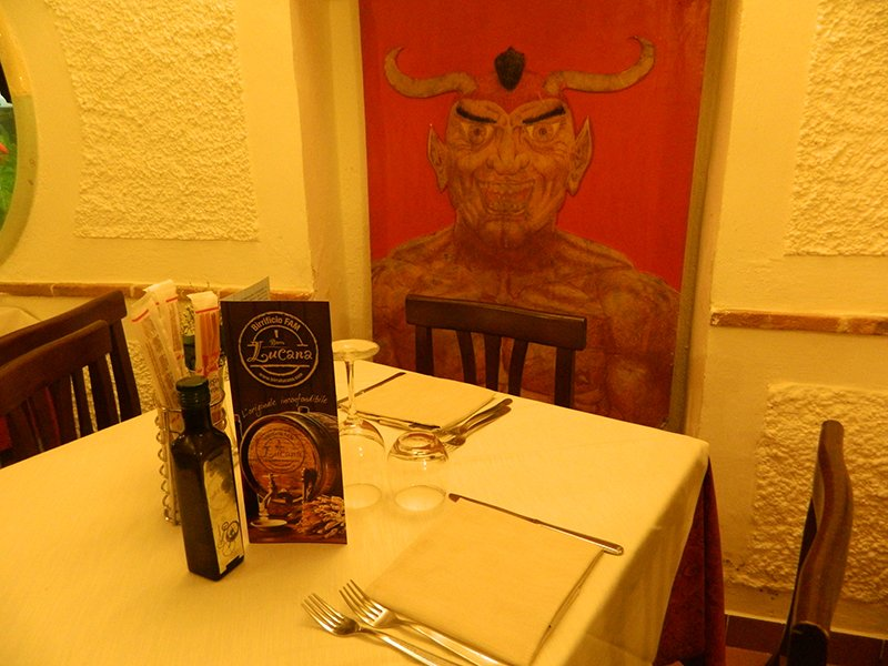 un tavolo apparecchiato e dietro l'immagine di Lucifero