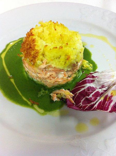 un tortino di riso giallo e salmone con della salsa verde e insalata rossa