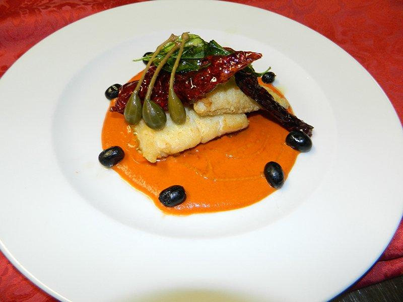 pesce su una crema arancione con verdure e olive