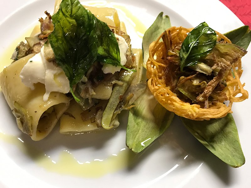 un piatto di cpasta decorata con erbe e verdure