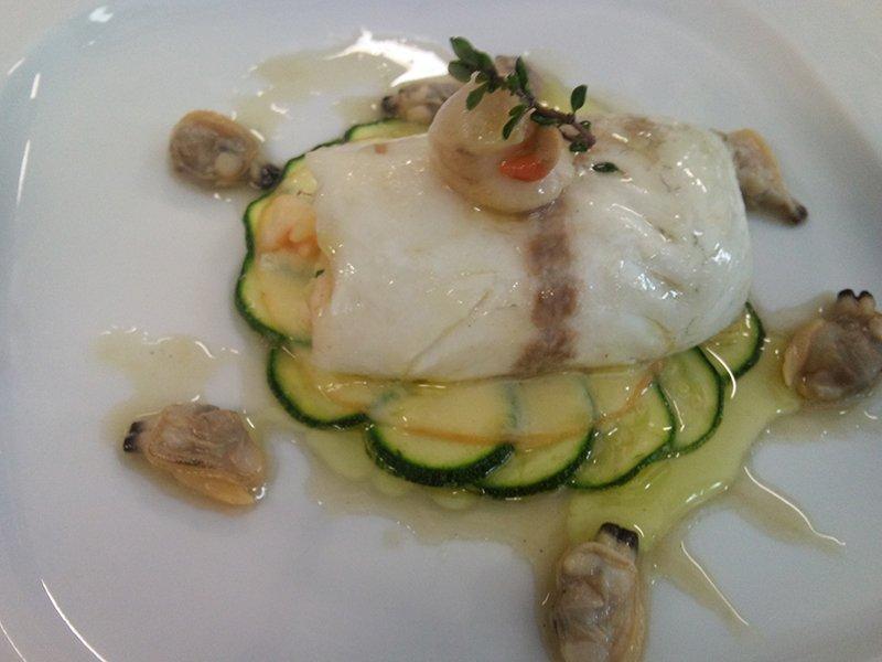 un piatto di carpaccio di pesce con zucchine e vongole