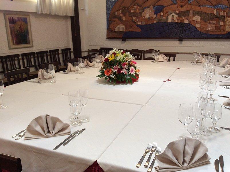 un tavolo apparecchiato con al centro dei fiori di diversi colori