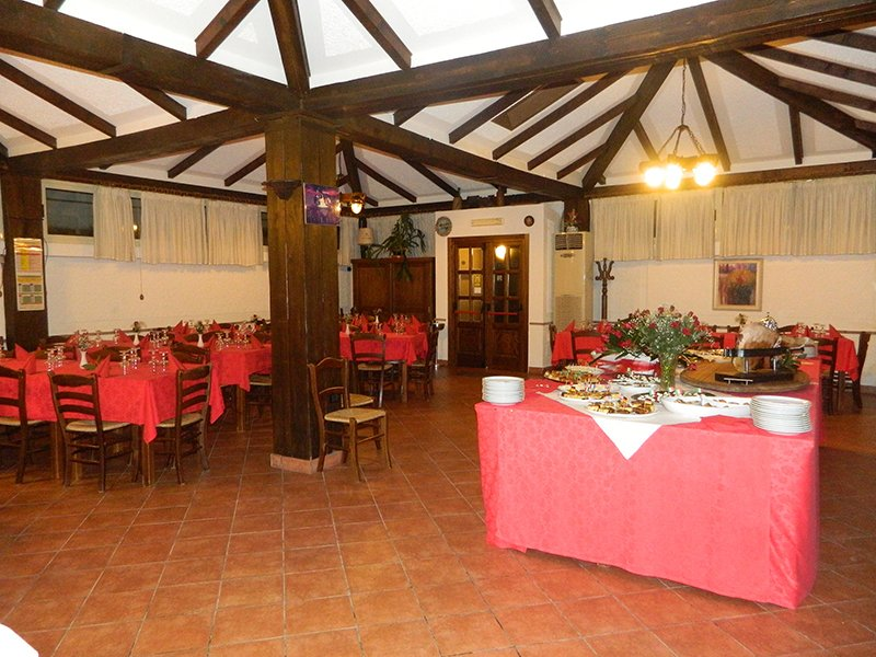 interno del ristorante con tavoli apparecchiati con tovaglie rosse