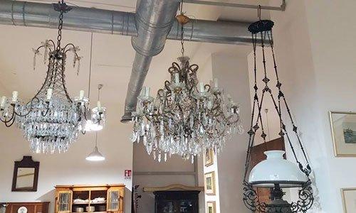 una serie di lampadari di cristallo appesi al soffitto e un tubo di acciaio