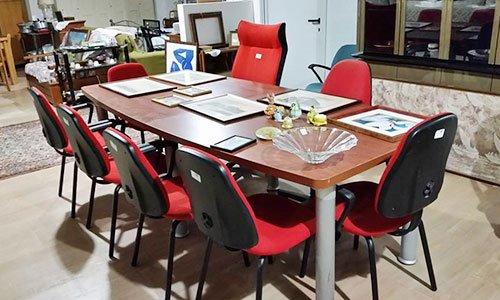 una scrivania di legno con attorno delle sedia da ufficio di color rosso