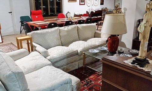 due divani bianchi a due posti,un tavolino in vetro con sopra una lampada e  altro arredamento esposto