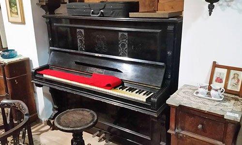 un pianoforte con sopra ai tasti una stoffa rossa e accanto altri mobili
