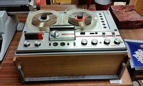 un antico stereo a due pellicole e di fianco una macchina da scrivere e altri oggetti