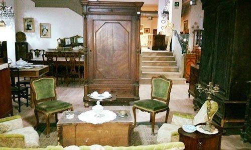 un mobile antico, delle sedie rivestite di velluto verde e altri mobili