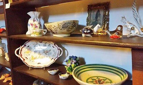 uno scaffale con delle mensole in legno conn sopra degli oggetti di porcellana e un pesce e uno scoiattolo di cristallo