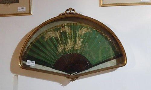 un tavolino di vetro con sopra la base di una lampada rossa e accanto altri mobili in legno