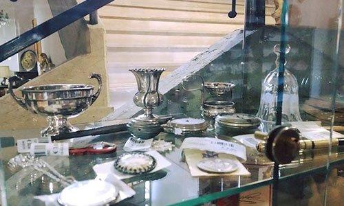 una vetrina allestita con una coppa d'argento,un porta vasi, una campanella di vetro e altri oggetti