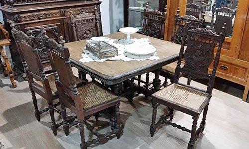 un tavolo in legno scuro antico con sei sedie e dietro un altro mobile antico