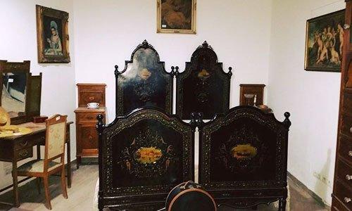 delle sedie antiche in legno scuro viste da dietro, una scrivania marrone con un cassetto e una sedia e dei quadri appesi al muro
