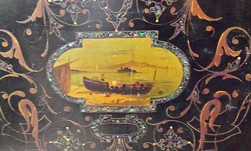 uno schienale di una sedia color nero con degli ornamenti rossi e verdi e al centro un segno di un uomo su una barca su uno sfondo giallo