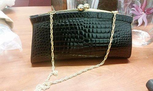 una borsetta di pelle color nero con manico e tracolla dorata