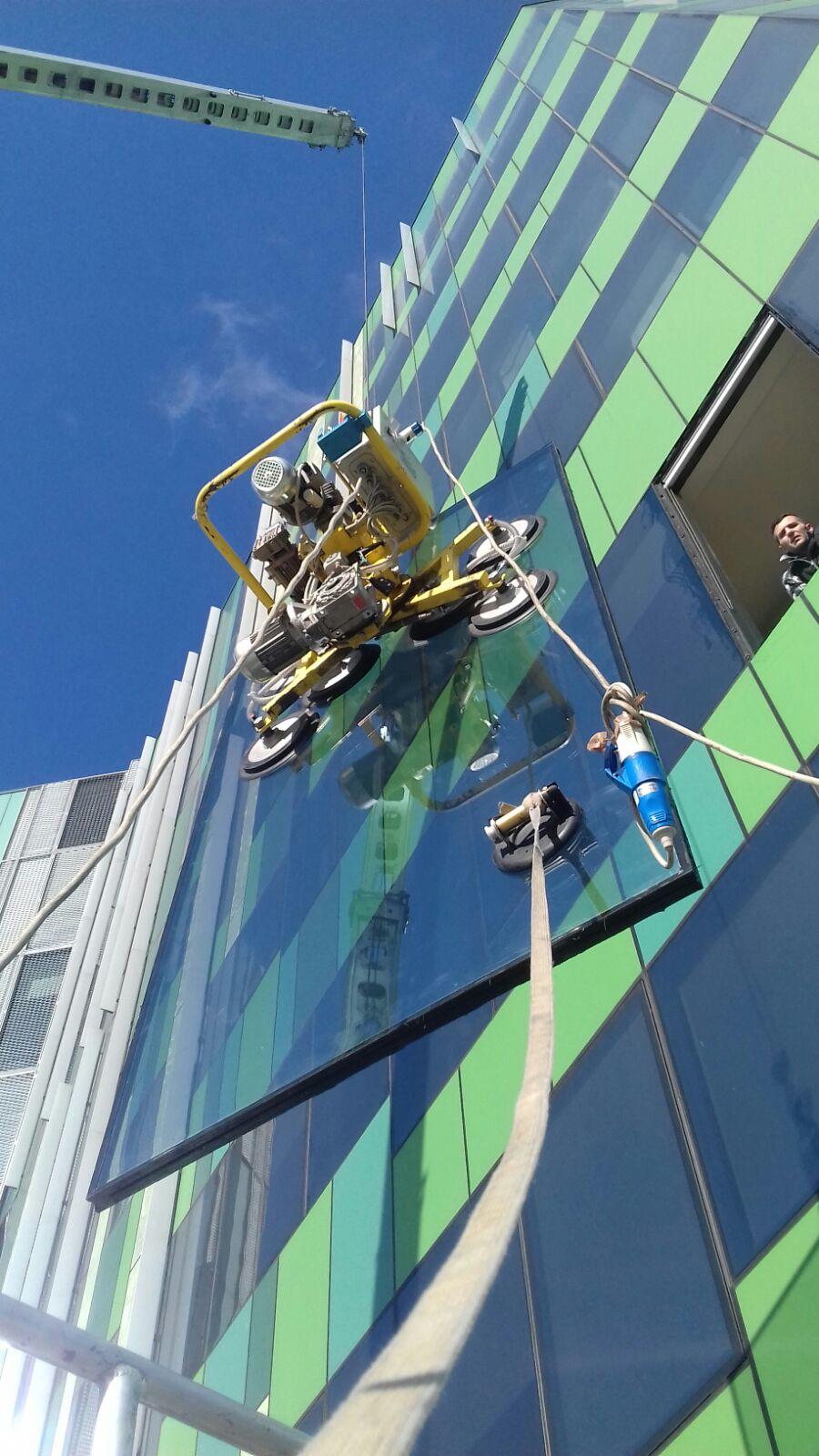Installazione della vetrata esterna di un palazzo con macchinario a ventose