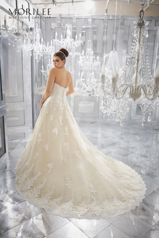 modella di spalle con vestito da sposa in pizzo ricamato di filo