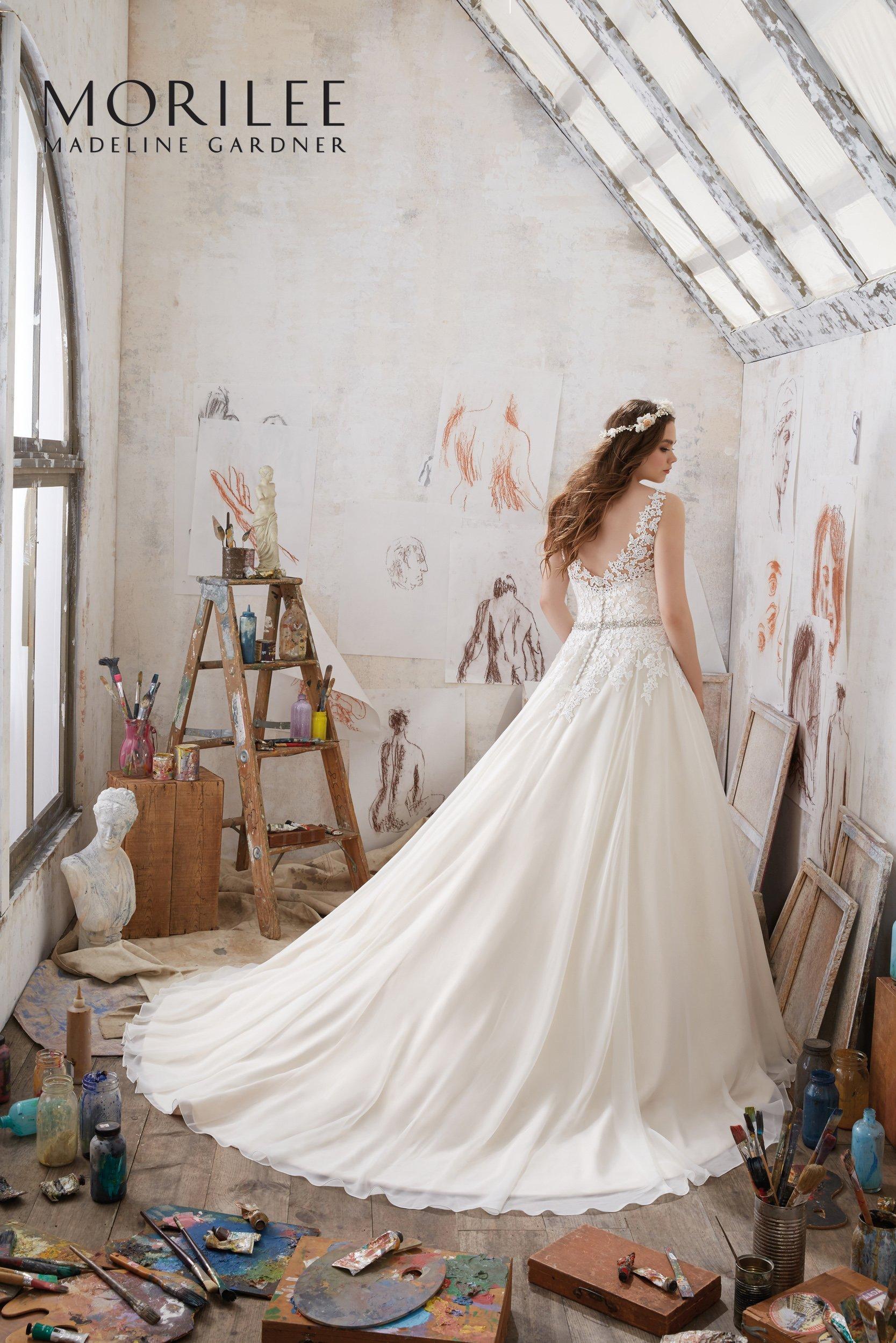 modella di spalle con vestito da sposa lungo con coda