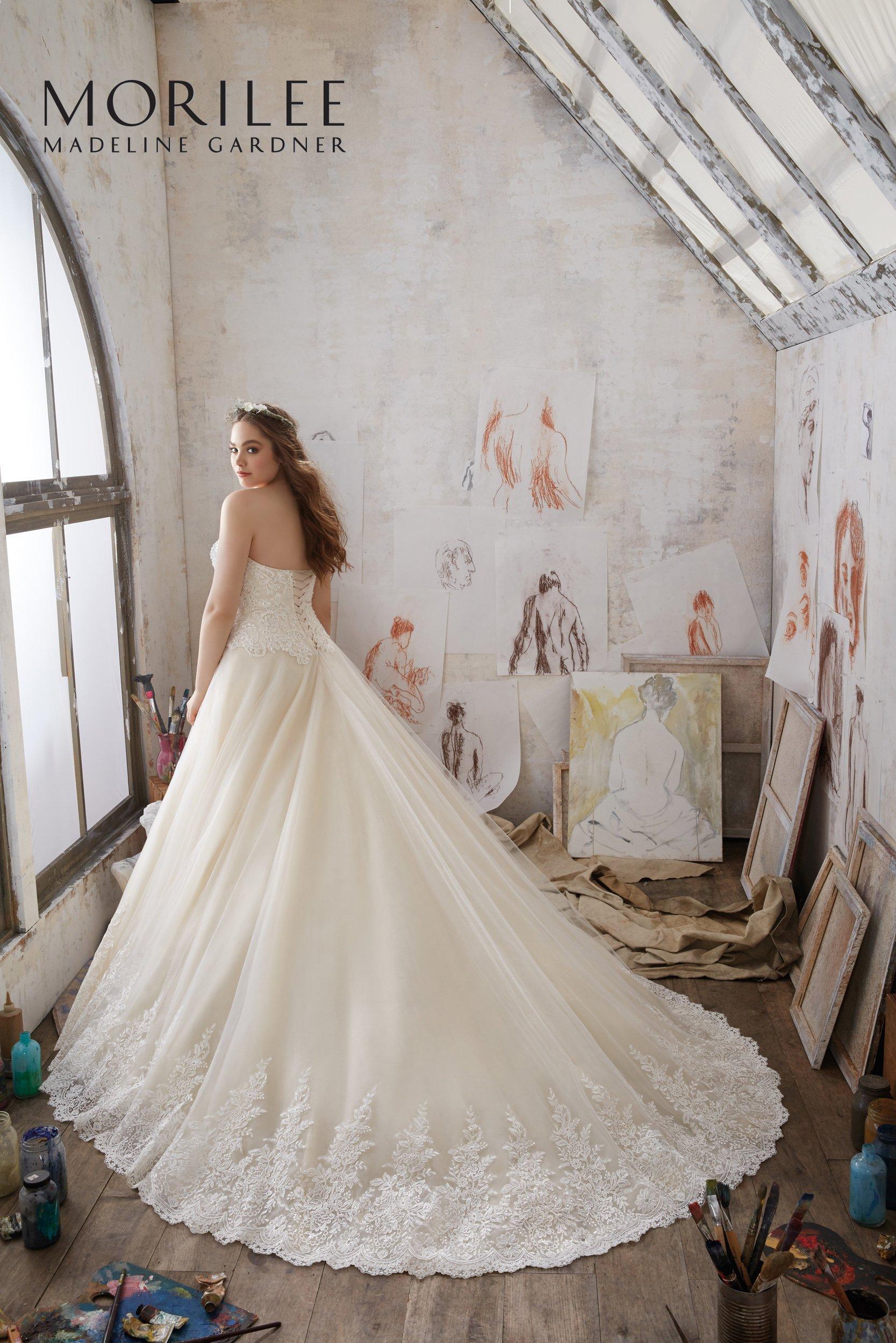 modella di spalle con vestito da sposa lungo con coda -vista laterale
