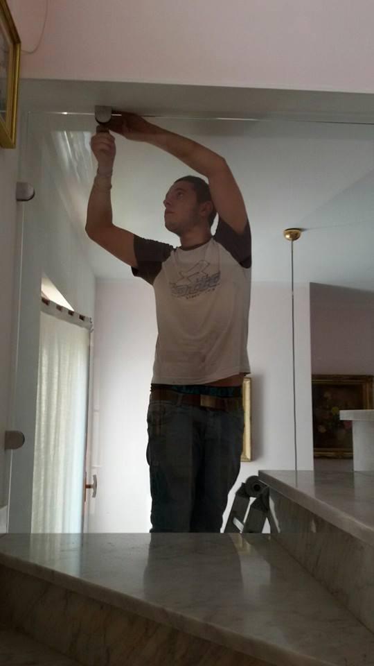 un uomo mentre installa una guida di una porta