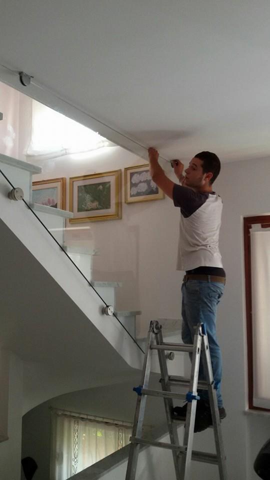 un ragazzo su una scala che installa una guida di una porta