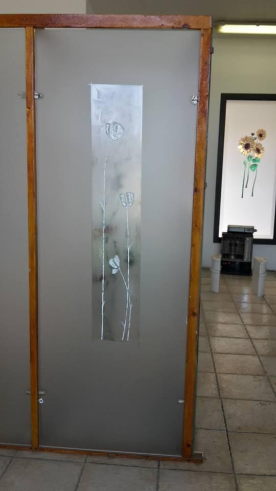 una porta in vetro con  disegni a fiori