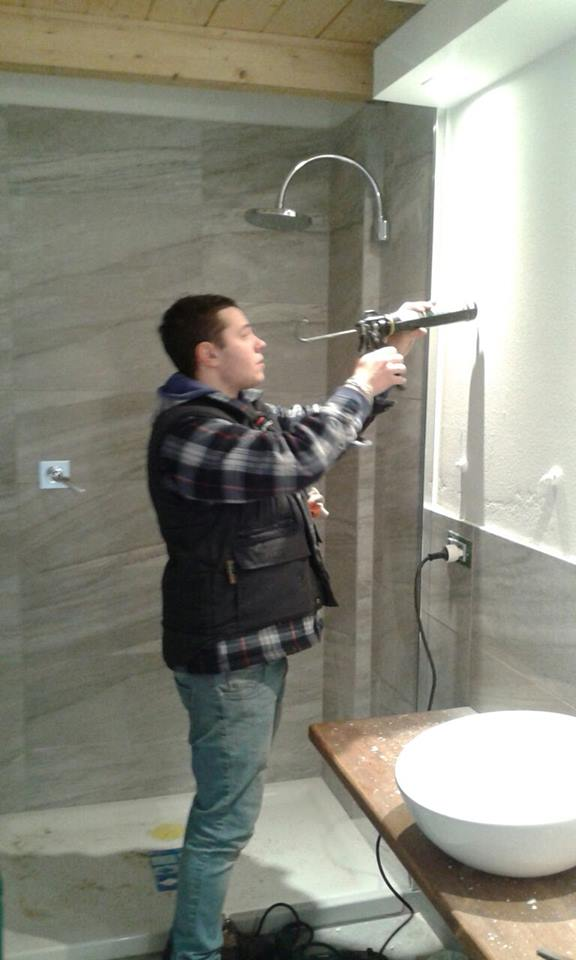 un operaio che applica del silicone vicino a una doccia