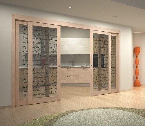 una porta a due ante scorrevoli in vetro e con finiture in legno beige