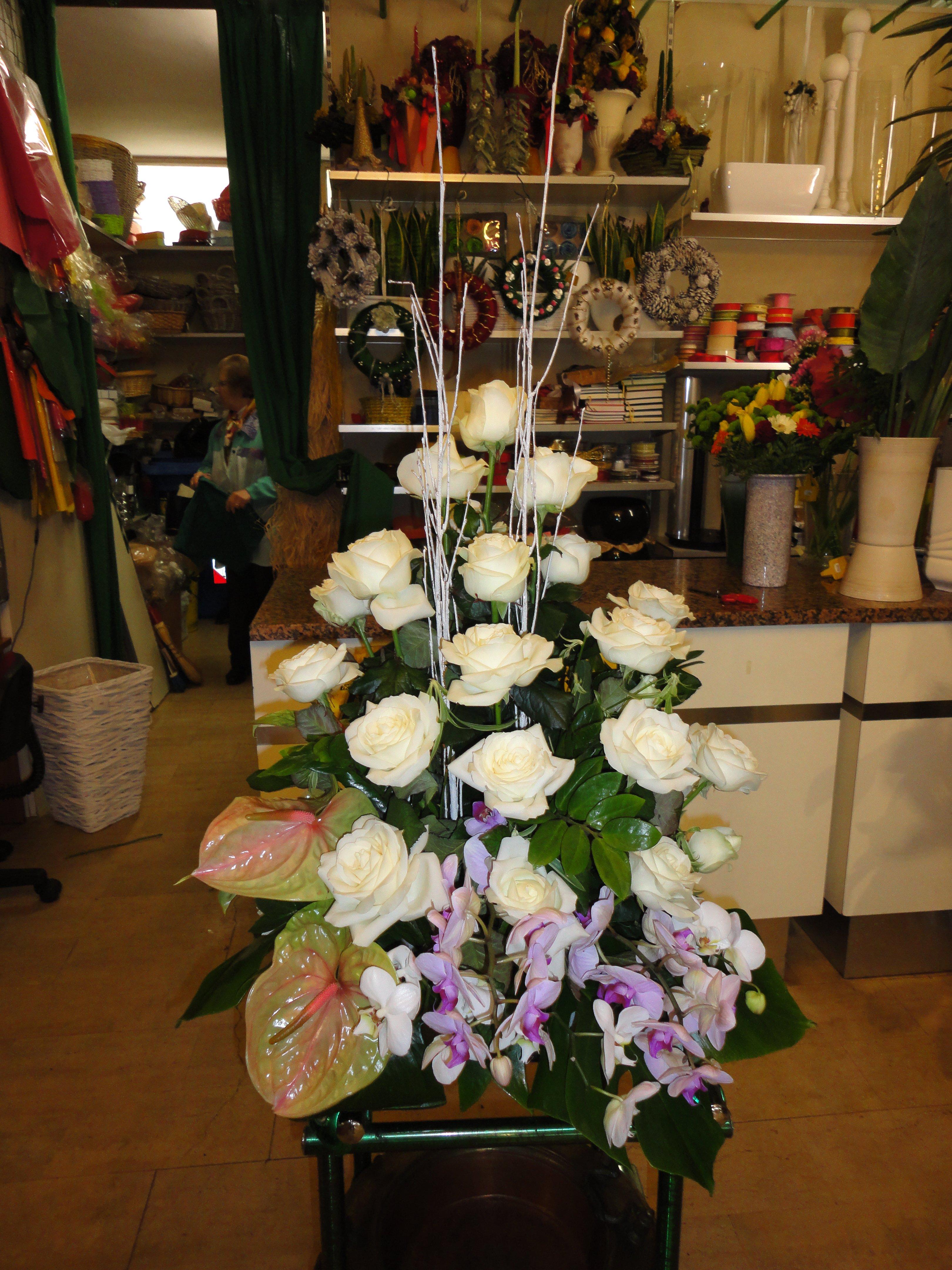 composizione di rose bianche dentro un fioraio