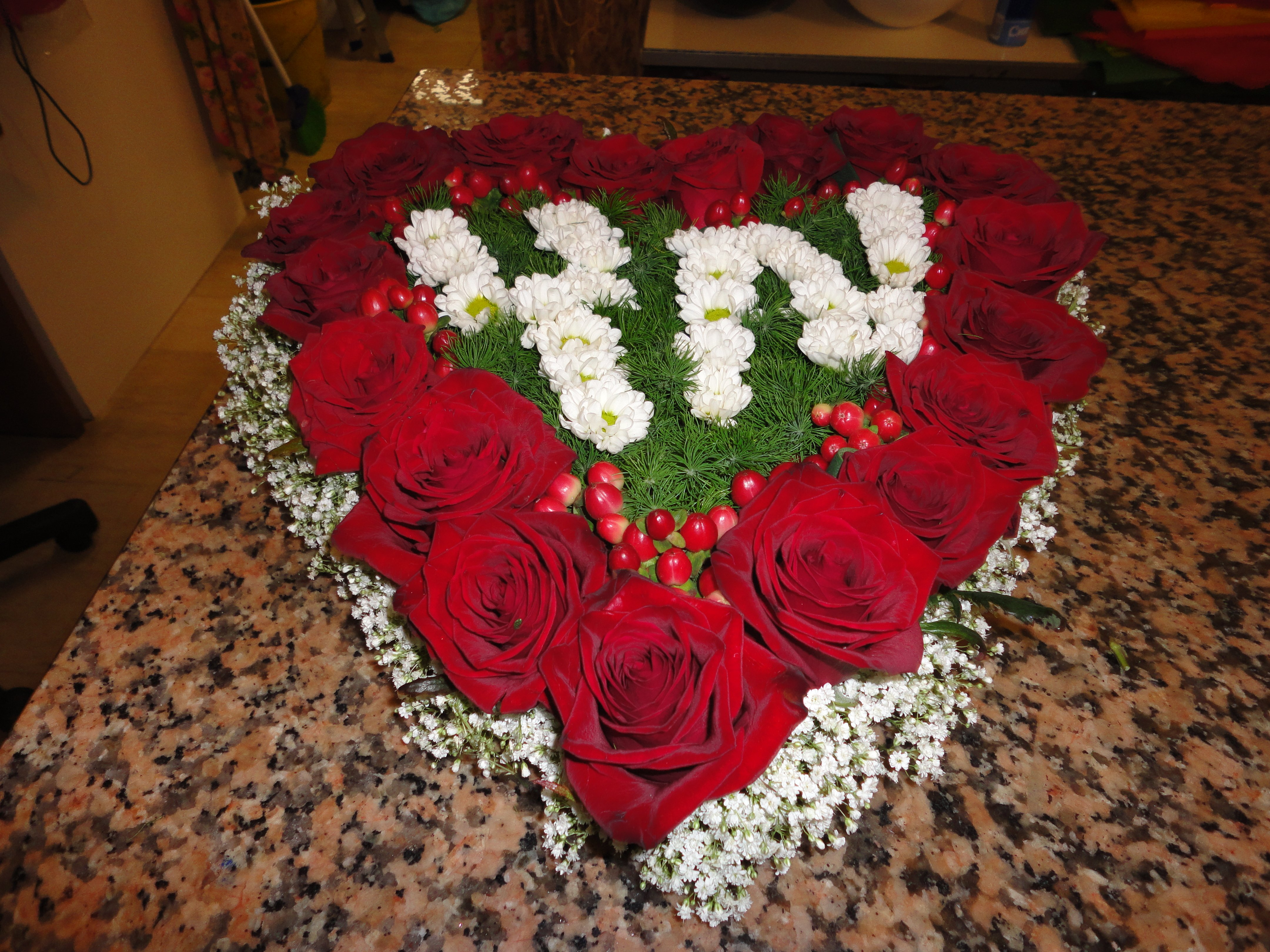 composizone floreale di rose rosse a forma di cuore