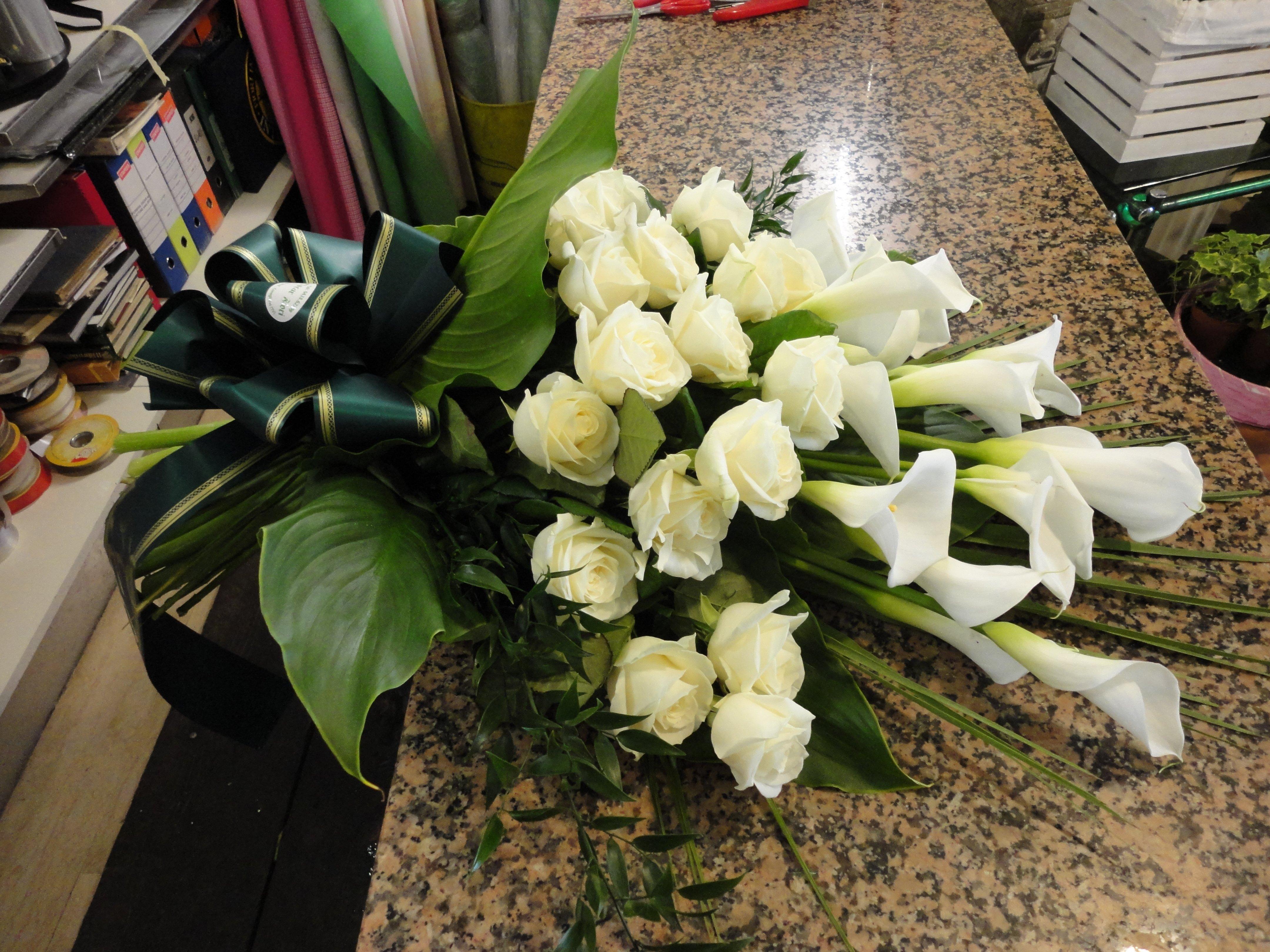 mazzo di rose e calle bianche appoggiate sul bancone di un negozio