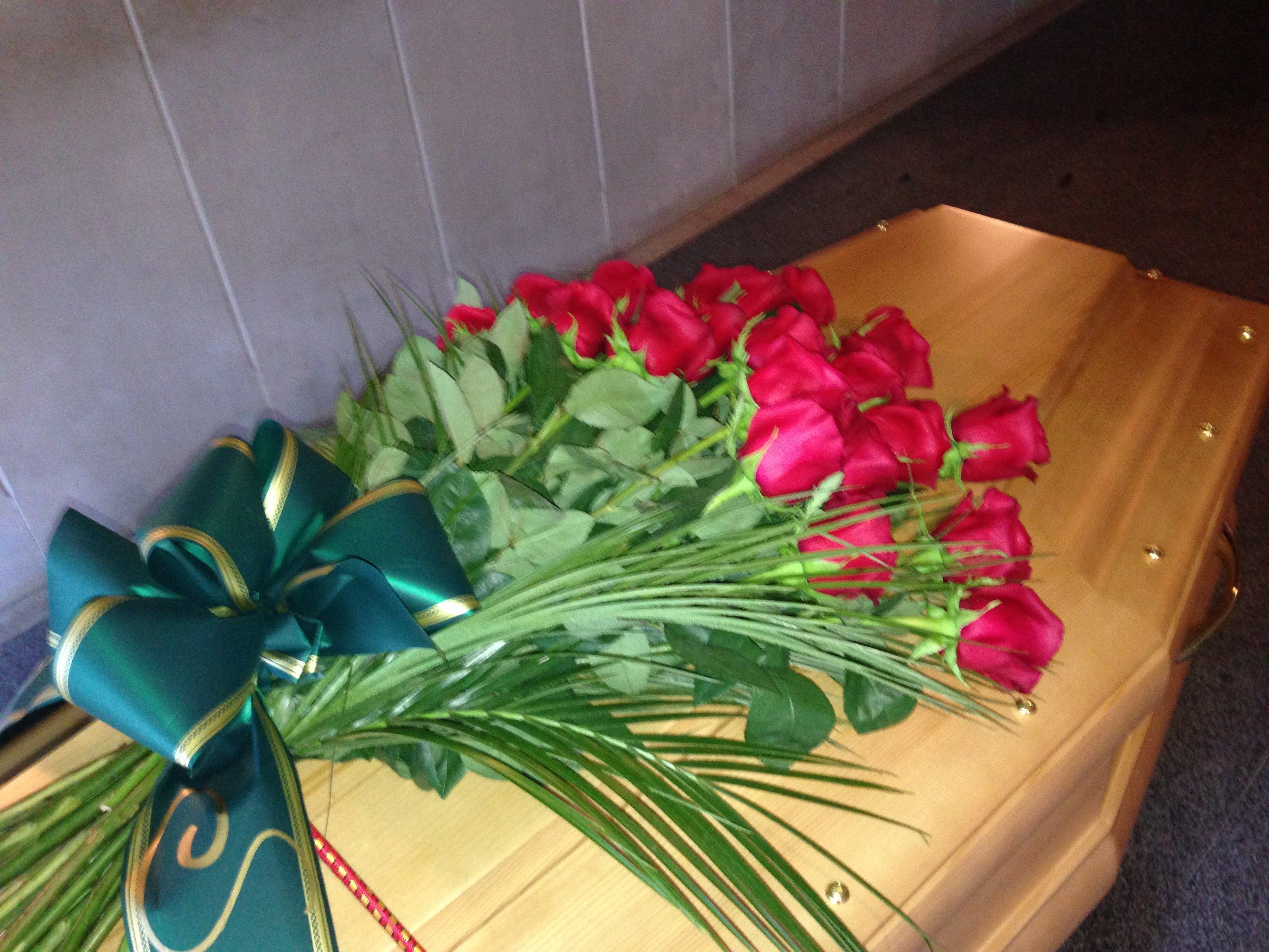 rose rosse su una bara