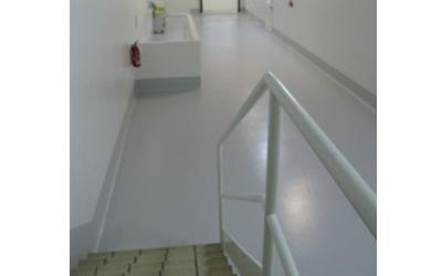 un corrimano, dei gradini e visto di un corridoio