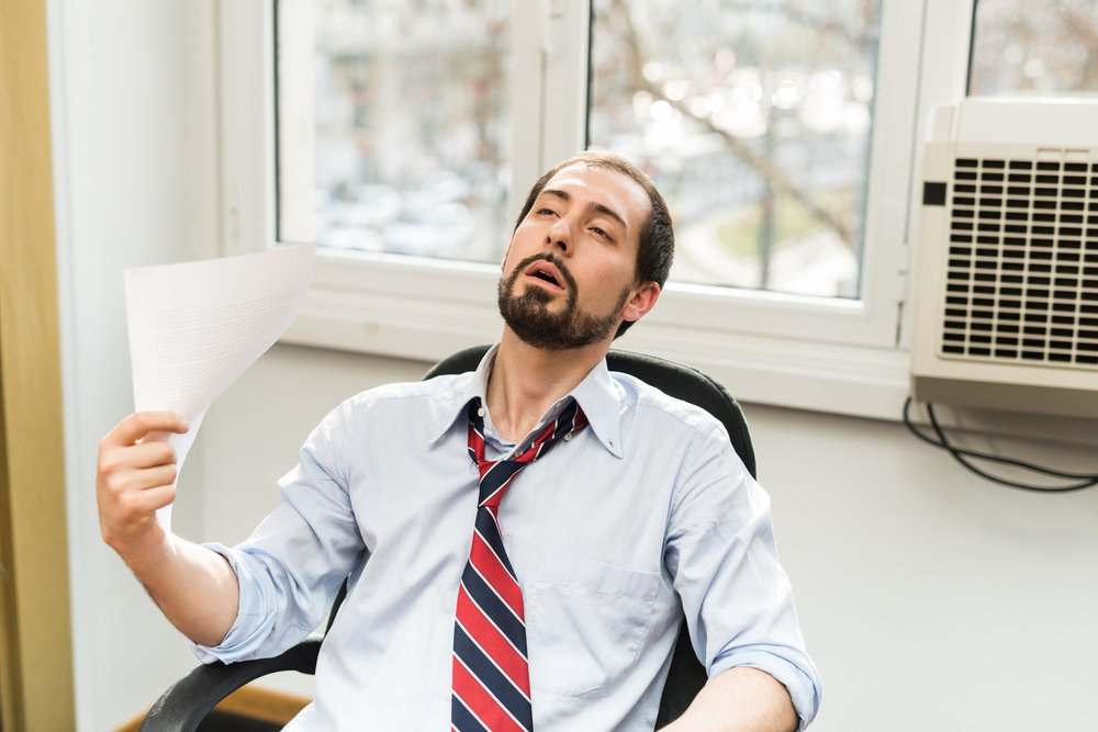 man hot in office with broken air conditioner