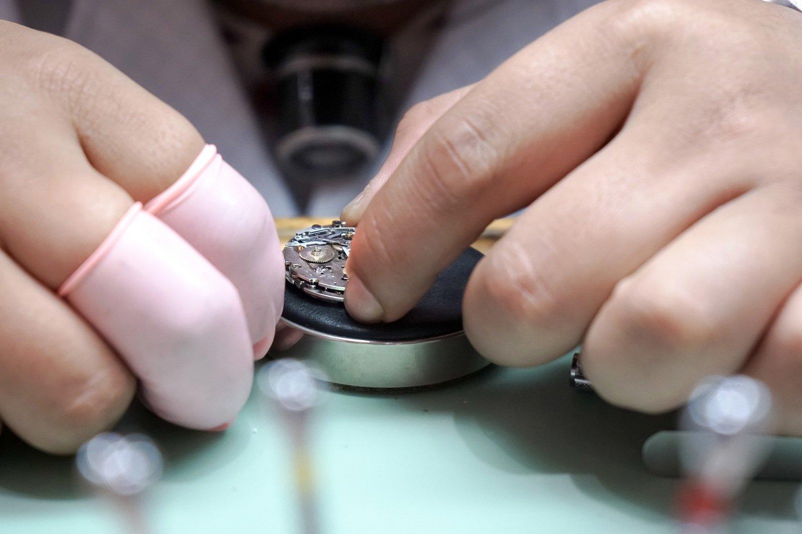 orologiaio che ripara un vecchio orologio da tasca