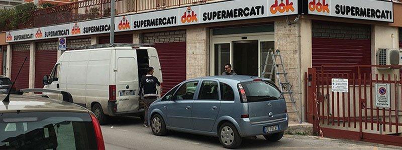 vista dall'esterno del supermercati Dok e delle macchine parcheggiate accanto