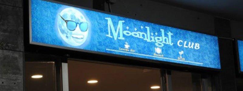 un cartellone con delle luci accesi con scritto Moonlight Club