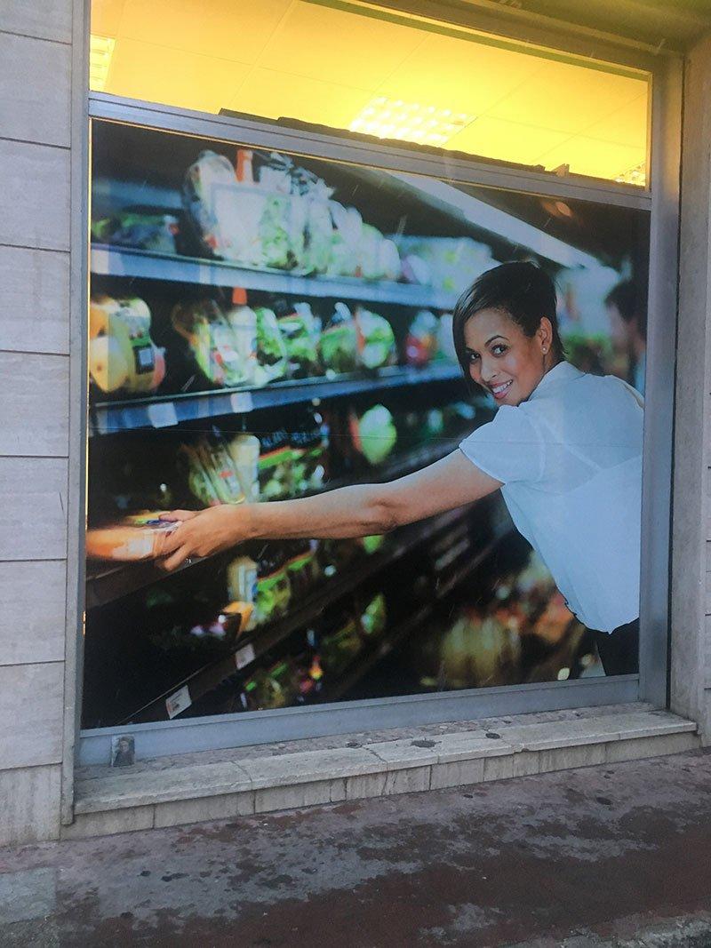 una vetrina del supermercato con un'immagine di una donna che prende un pacco da uno scaffale di un supermercato