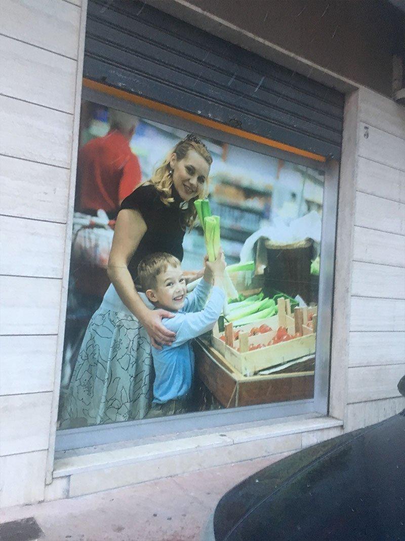 una vetrina del supermercato con un'immagine di una un bambino e la sua mamma al supermercato