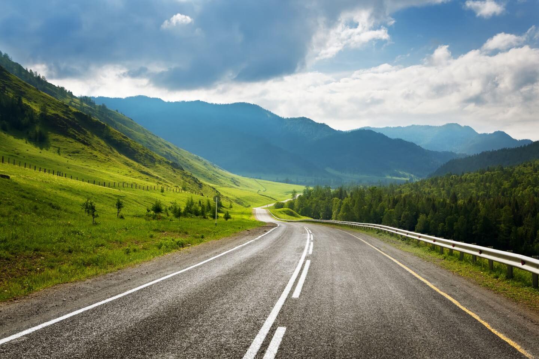 strada con alberi ai lati e vista sulle montagne