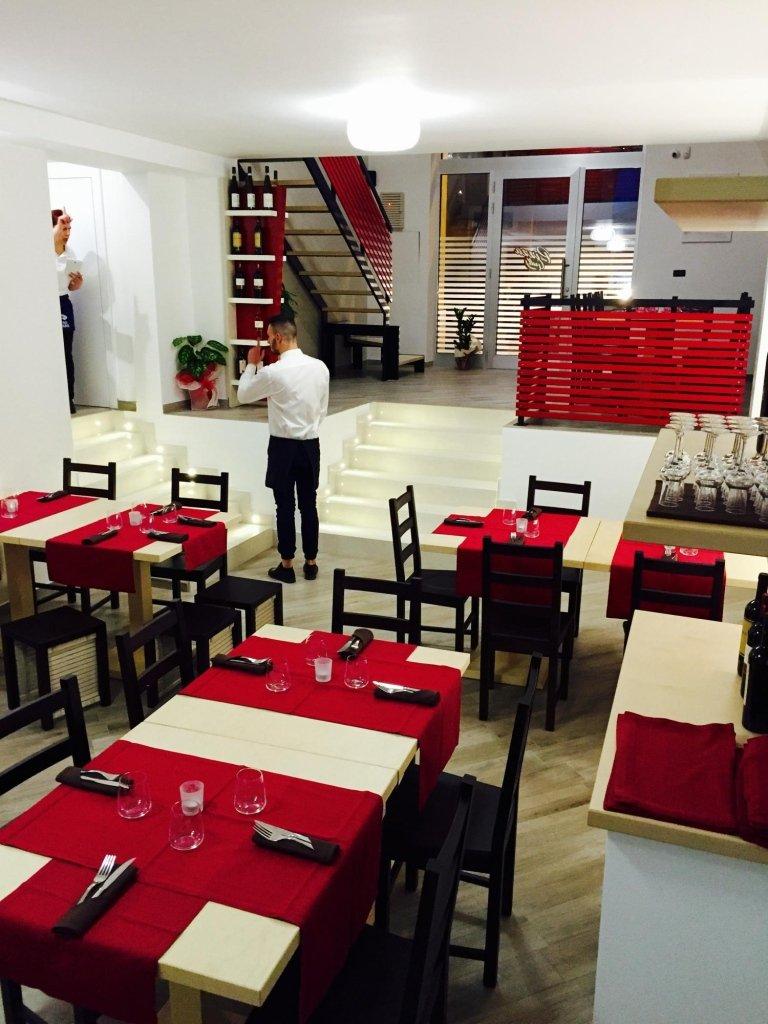 i tavoli all'interno del ristorante e un cameriere