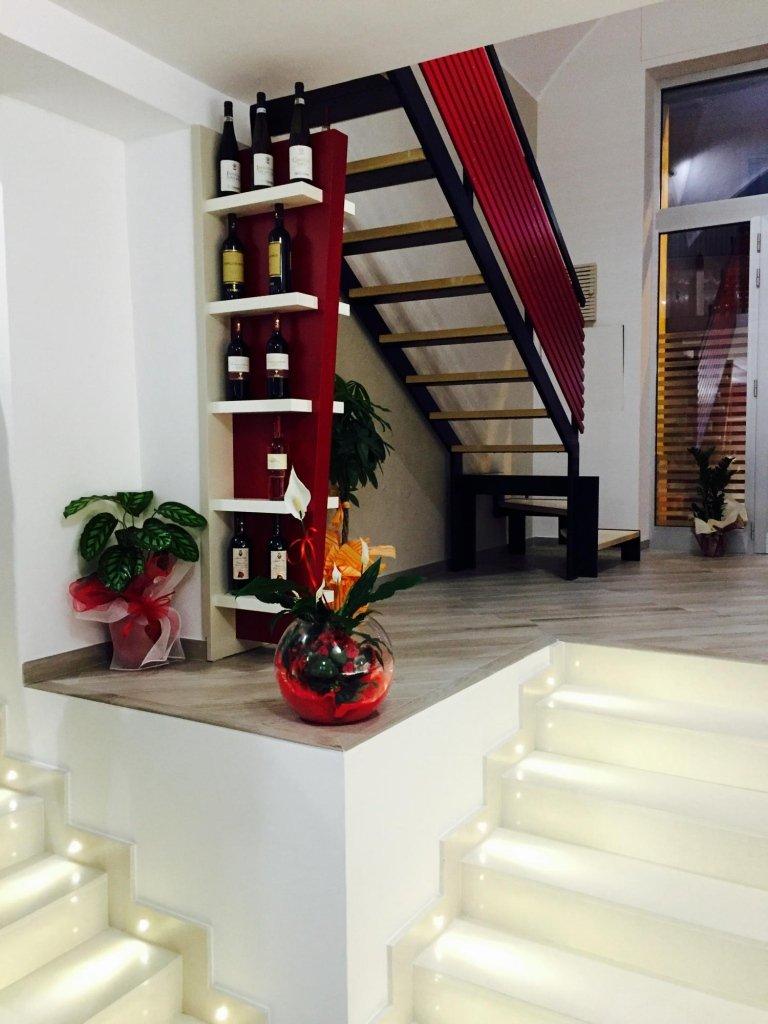 uno scaffale con dei vini, due vasi con delle piante e delle scale