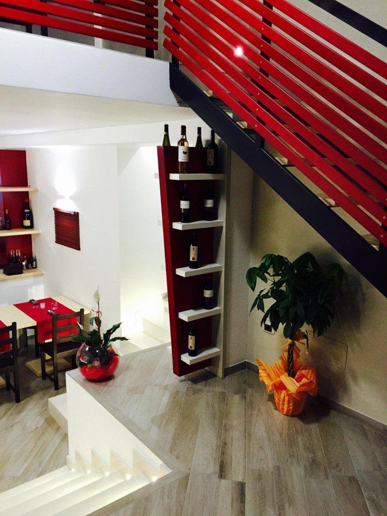 una pianta, uno scaffale con dei vini e delle scale