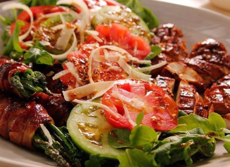 un piatto di insalata, pomodori e carne