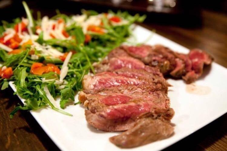 una tagliata di carne e dell'insalata mista