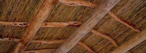 Controsoffitto con travi grezze e bambù