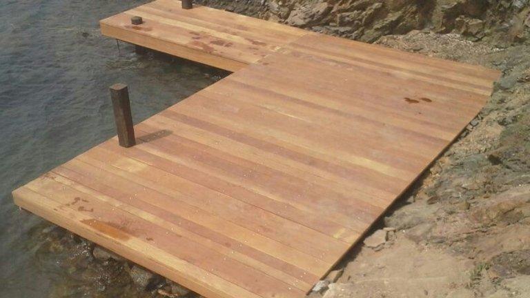 Passerella in legno chiaro con travi rettangolari per accesso al mare